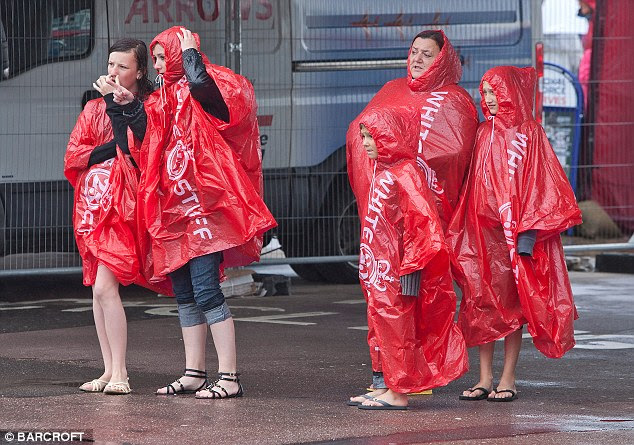 Summer-wear: Tourists in Bournemouth, Dorset, after the downpour today