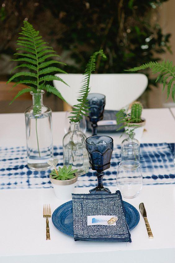 eine shibori-indigo Tischläufer, Gläser, bedruckte Servietten und Platten für einen boho Wald Hochzeit