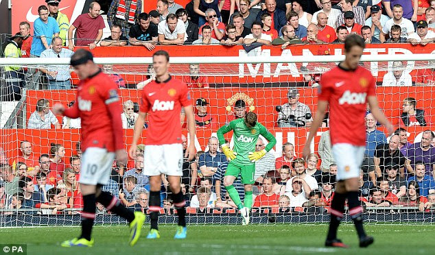 Toppled: Manchester United's players including goalkeeper David De Gea stand dejected