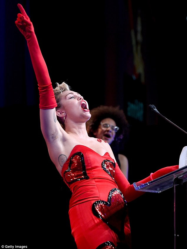 Revving up the crowd: Miley was clearly very passionate about what she had to say, as she threw her red gloved arm up into the air and shouted dramatically