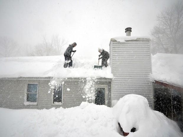 Tami Normile e Richard Brooks tentam tirar o excesso de neve do telhado de sua casa no subúrbio de Lakeview, em Buffalo, NY, na quinta-feira (20) (Foto: John Normile/Getty Images/AFP)