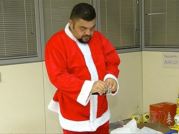 Funcionário se prepara para virar o Papai Noel (Foto: Reprodução/TV Anhanguera)