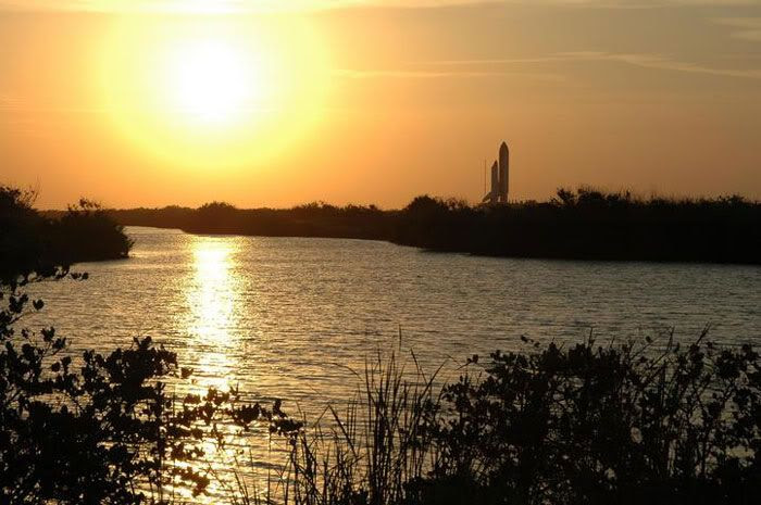 Space Shuttle Discovery rolls out to its launch pad as the Sun sets.