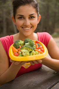 Mujer con un plato de verduras frescas