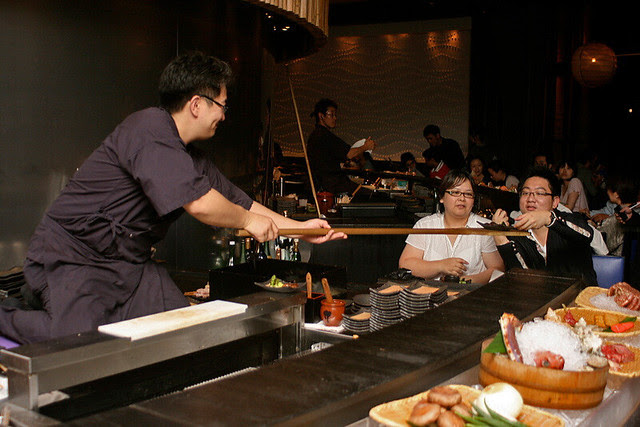 The chef delivers the food using the wooden oar or paddle