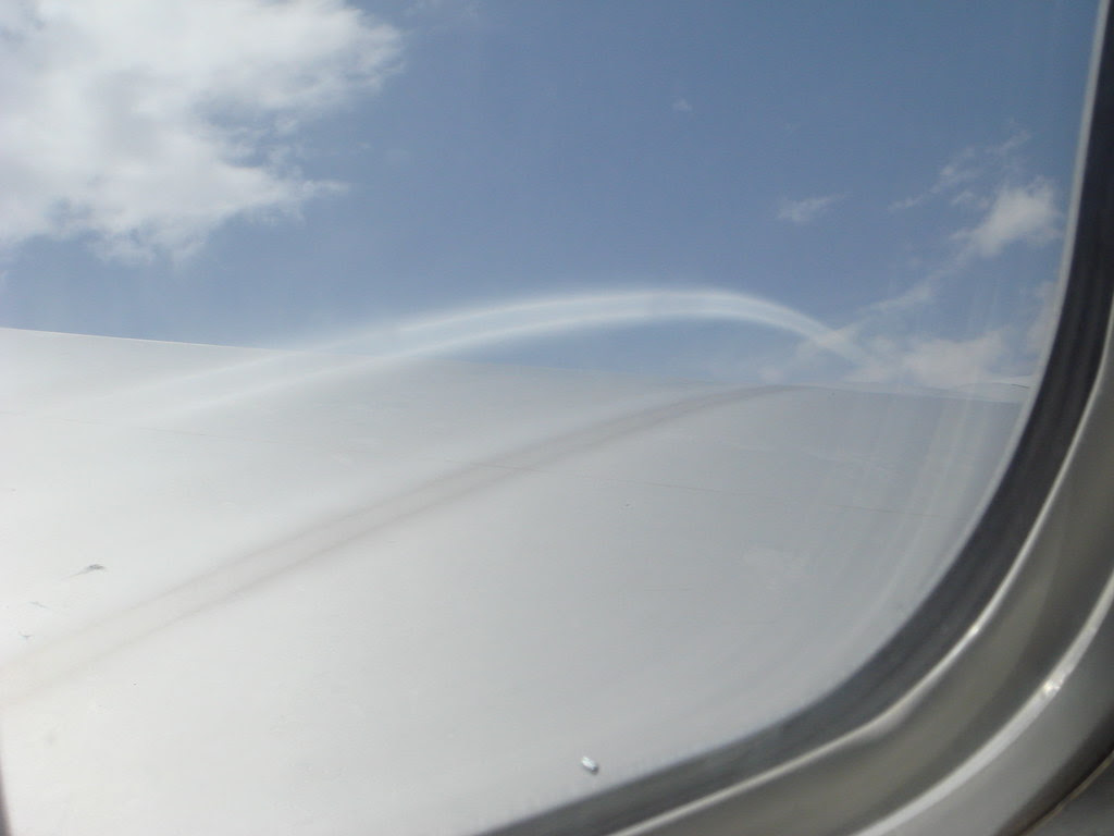view out of an airplane window, with a weird vapor arc thing