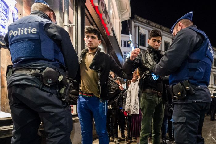 Police officers check people as they enter the Grand Place in Brussels on Thursday. Belgian officials canceled the capital's New Year's Eve fireworks display and all official events there because of a threat of a terrorist attack.