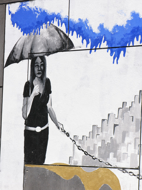 mural with woman holding umbrella, Kenmare Street, Manhattan, NYC