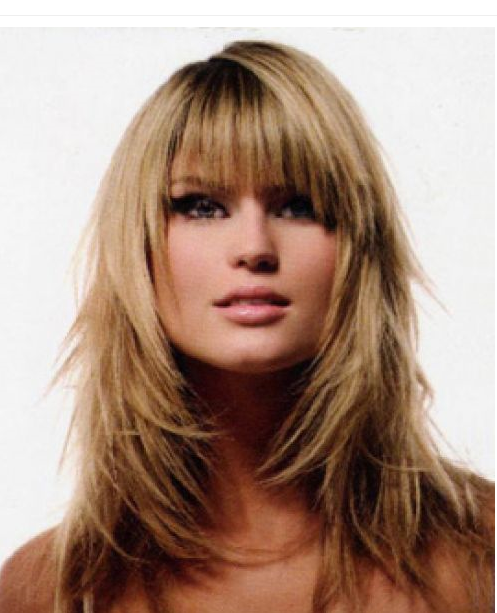 Long full layered woman hairstyle with long bangs.
