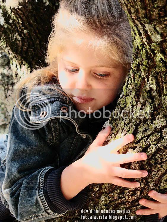 Una niña sueña despierta abrazada al tronco de un arbol