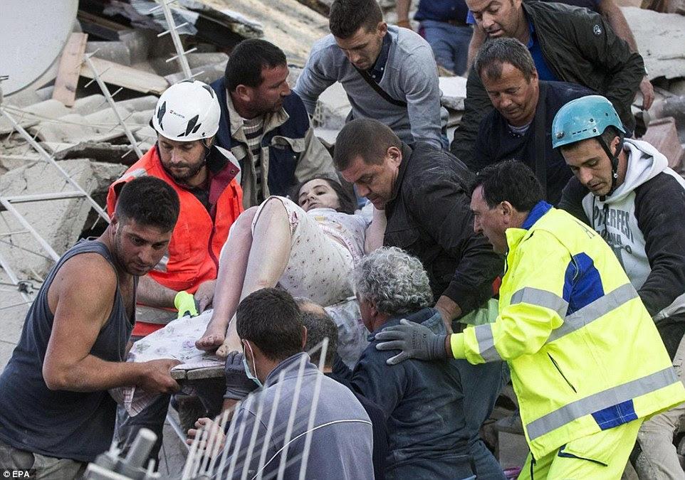 Uma mulher ferida em suas roupas de noite é realizada por equipes de resgate entre os escombros dos edifícios derrubados em Amatrice