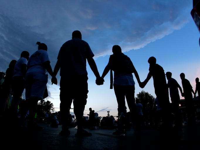 People pray after marching about a mile to the police station to protest the shooting of teenager Michael Brown on Aug. 20 in Ferguson, Mo. Brown's shooting on Aug. 9 by a Ferguson police officer has sparked a more than week of protests, riots and looting in the St. Louis suburb.