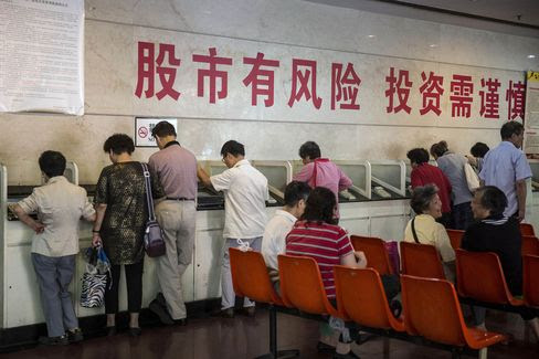 """Investors stand at trading terminals under a slogan """"The Stock Market has Risks, Use Caution When Investing"""" at a securities exchange house in Shanghai, China, on Friday, Sept. 18, 2015. China's stocks headed for the steepest weekly loss this month in shrinking turnover amid growing concern government measures to support the world's second-largest equity market and economy are failing. Photographer: Qilai Shen/Bloomberg"""