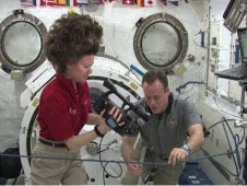 Cady Coleman and Ron Garan measure the orbiting radius of a water droplet