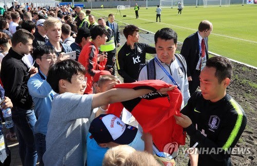 South Korea's Moon Seon-min (R) sign his autograph for fans after training at Spartak Stadium in Lomonosov, a suburb of Saint Petersburg, on June 13, 2018. (Yonhap)