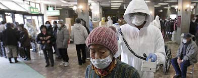 A woman is scanned for radiation exposure at a temporary scanning center for residents living close to the quake-damaged Fukushima Dai-ichi nuclear power plant Wednesday, March 16, 2011, in Koriyama, Fukushima Prefecture, Japan. (AP Photo/Gregory Bull)