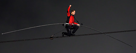 Nik Wallenda pumps his fist on one knee as he nears completion of his 1,800 feet-long tightrope walk over the brink   of the Niagara Falls in Niagara Falls, Ont., on Friday, June 15, 2012. (AP Photo)