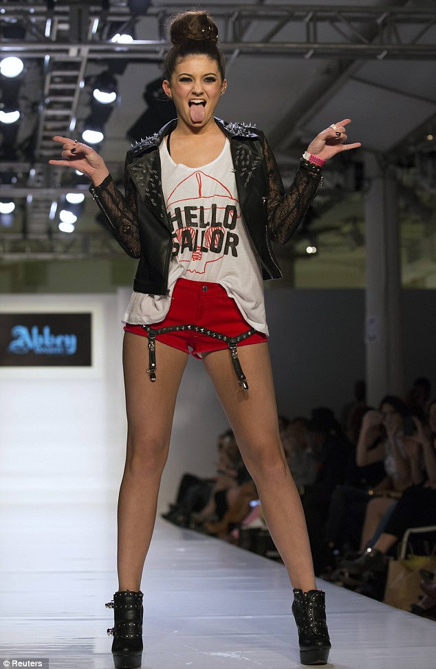 Attitude: Kylie sticks her tongue out at the end of the catwalk as she flicks rock horns