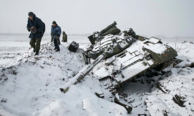 Members of the separatist self-proclaimed Donetsk People's Republic army collect parts of a destroye