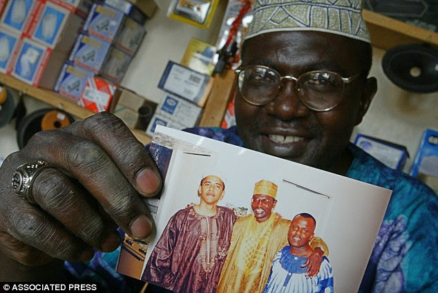 The Obama brothers have had a strained relationship over the years. In the above September 14, 2004, file photo, Malik Obama holds a picture of him and Barack Obama in his shop in Siaya, Kenya