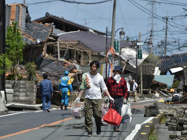 Moradores tentam retirar objetos de suas casas destruídas após terremoto em Mashiki (Kumamoto), neste domingo (17).  (Foto: AFP)