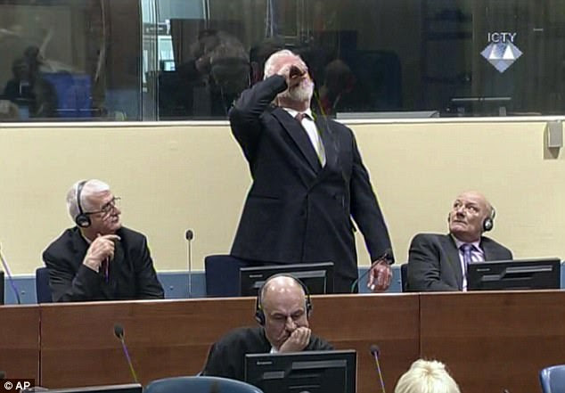 Protest: Fellow convicts Bruno Stojic and Milivoj Petkovic, sitting on either side of the Croat politician, look on in shock and surprise as he downs the contents of the bottle