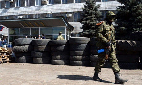 Armed men stand guard in front of a regional administrative building seized last night by pro-Russian separatists in the eastern Ukrainian city of Konstantinovka.