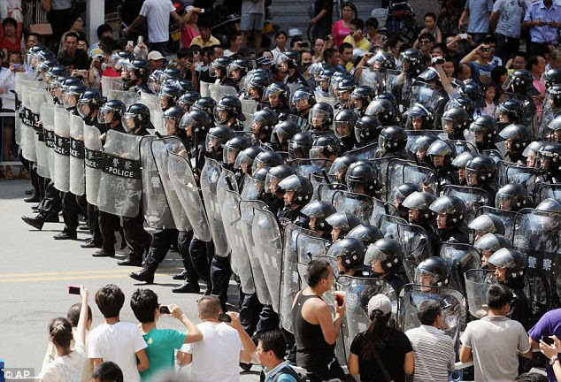 Armed: Police arm themselves in riot gear as they prepare to push back protesters