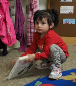 Sherlyn Hernández grabs a book at the Pajaro Valley Unified daycare center in Watsonville.