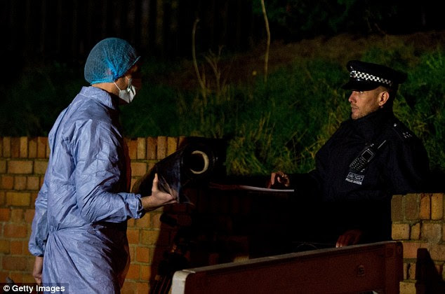 Work: A forensic officer carries items into Ms Blake's family home in Erith, London, following the discovery