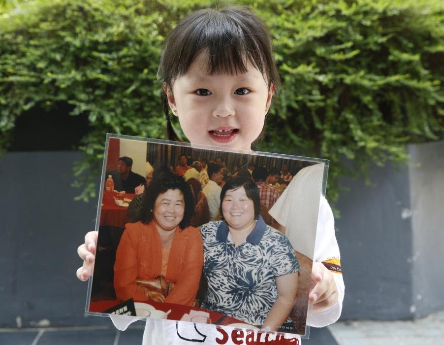 Jie Yie holds a picture of her grandmother Lee Sew Chu and her aunt Ng May Li who were aboard missing Malaysia Airlines flight MH370, on the one year ...