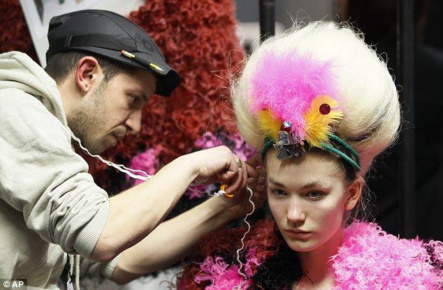 Por trás das cenas: Um cabeleireiro coloca alguns toques finais a peruca de um modelo