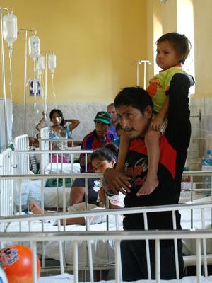O pai Leonidas Pacunda com o filho, Isbac, que carrega um feto em seu abdômen. (Foto: Karel Navarro / AP Photo)