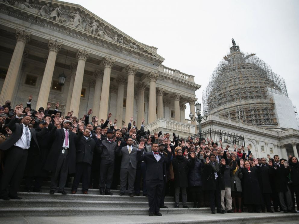 PHOTO: Black congressional staffers hold their hands up during a walkout to protest the recent Mike Brown and Eric Garner grand jury decisions on Dec. 11, 2014 on the steps of the U.S. Capitol in Washington, DC.