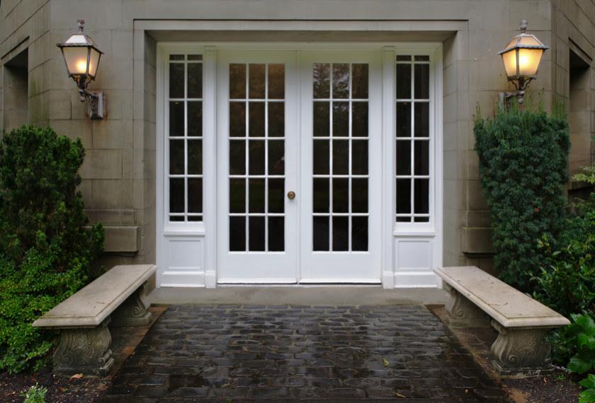 Elegant entrance doors with stone walkway and bordering seats e1429297678262