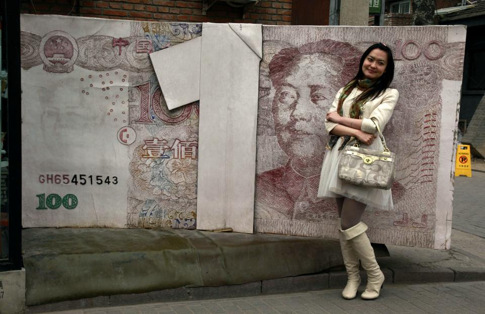 FILE - In this March 15, 2012 file photo, a Chinese woman poses for photos near a sculpture depicting a Chinese yuan note at an art district in...