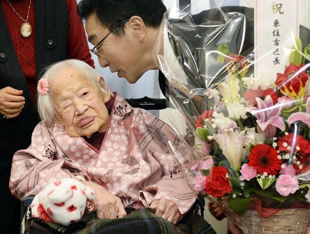 """""""Parece ter sido bastante curto"""", disse Misao após receber um buquê de flores de um oficial do governo que lhe perguntou como se sentia sobre viver tanto tempo.  (Foto: Kyodo/AP)"""