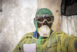 A health worker examines patients for Ebola inside a screening tent, at the Kenema Government Hospital situated in the Eastern Province around 300 km, (186 miles), from the capital city of Freetown in Kenema, Sierra Leone, Monday, Aug. 11, 2014. (AP Photo/ Michael Duff)