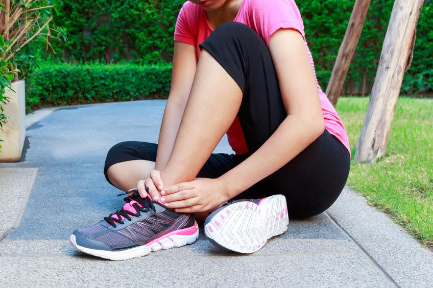 Người phụ nữ thể thao châu Á bị bong gân mắt cá chân khi chạy bộ hoặc chạy