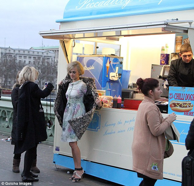It's never ending! In yet another outfit change, Fearne donned this floral dress as she posed by a hot dog stand
