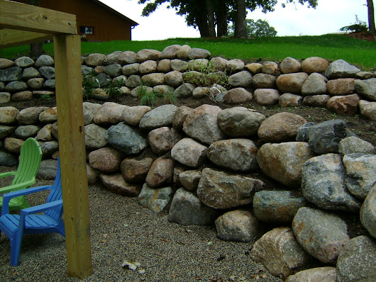 Boulder Retaining Wall with Patio and Paver Stair Case - Oasis Landscapes