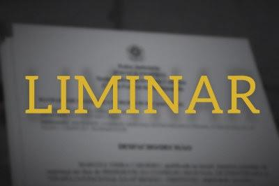 Imagem de documentos em desfoque ao fundo com letreiro amarelo escrito Liminar em primeiro plano.