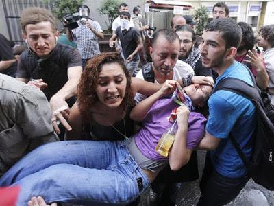 Una manifestante herida es evacuada por varios participantes durante una protesta contra la construcción de un centro comercial en la Plaza Taksim, en Estambul. EFE