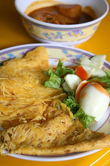 Roti Jala with boiled egg, salad and curry chicken in bowl