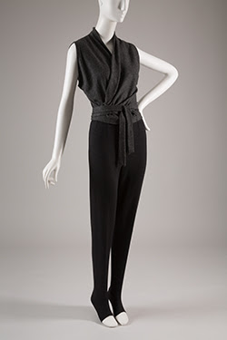 black top with with wrap around belt and long black pants