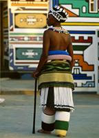 A Ndebele bride dresses in the beaded leg and waist hoops and skirts that constitute her bridal outfit, South Africa
