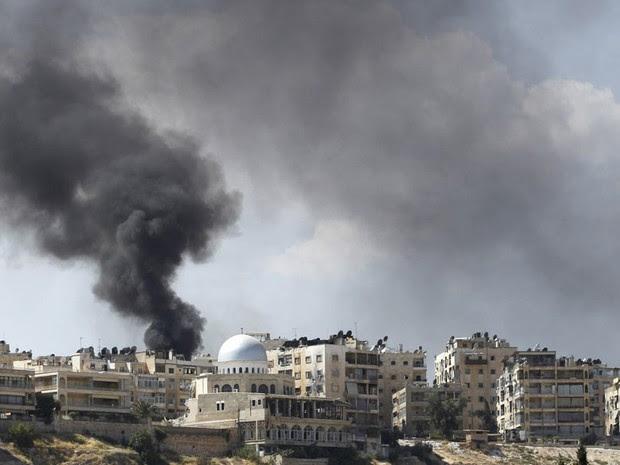 Fumaça escura ganha o céu sobre o distrito de El Edaa, na cidade síria de Aleppo, após um bombardeio feito por um jato da Força Aérea Síria, em combate contra rebeldes que tentam tomar a cidade. (Foto: Youssef Boudlal/Reuters)