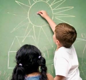 Menino desenha casa e sol na lousa e menina observa, ambos de costas para a camera