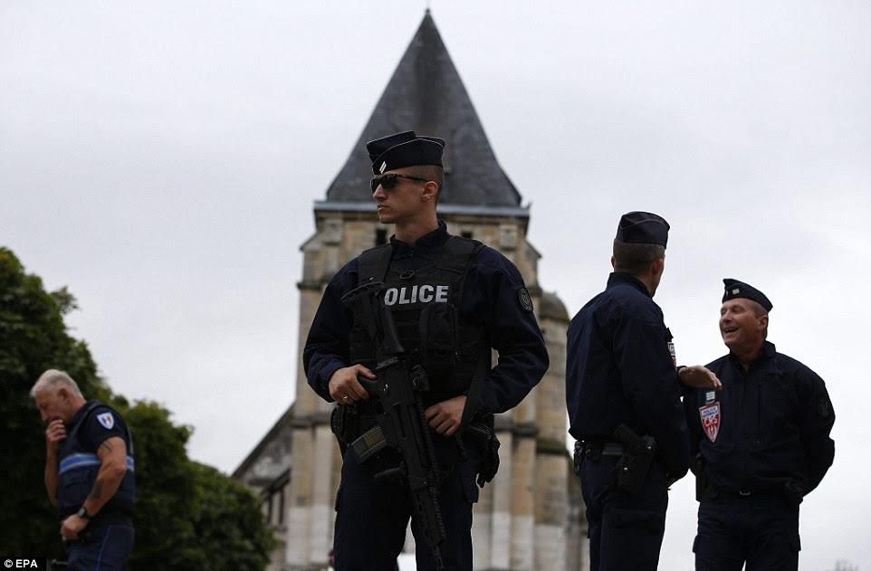 Os agentes da polícia proteger o perímetro em torno da igreja na quarta-feira de manhã como investigações continuam sobre o assassinato do padre