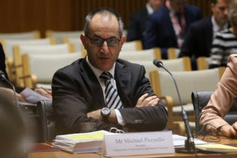 Mike Pezzullo wears black framed spectacles, a brown suit and striped tie as he crosses his arms in a senate estimates hearing.